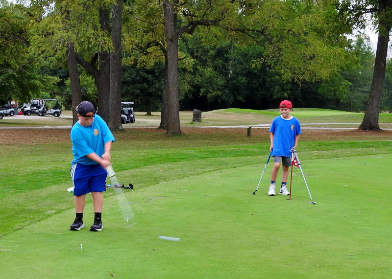 2 future Rotarians practicing their putting skills